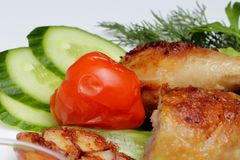 Stekt kycklingben med grönsaker i en platta arkivfoton