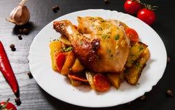 Stekt kycklingben med morötter, lökar och potatisar tjänade som på en vit platta fotografering för bildbyråer