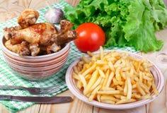 Stekt kycklingben, potatis och grönsaker på trätabellen Arkivfoton