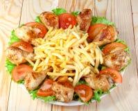Stekt kycklingben, potatis och grönsaker på trätabellen Royaltyfria Bilder