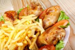 Stekt kycklingben, potatis och grönsaker på trätabellen Royaltyfri Foto