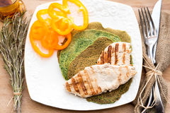 Stekt kycklingbröst med spenatpannkakor och gul paprika Royaltyfri Fotografi