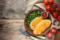 Stekt kycklingfilé med ostskorpan och garnering av ny vege royaltyfria foton