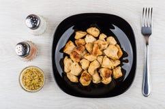 Stekt kycklingkött i plattan, gaffel, senap som är salt, peppar Arkivfoto