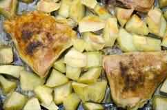 Stekt kycklinglår med potatisar på ett bakplåtslut upp Royaltyfri Fotografi