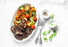 Stekt kycklinglever och bakade säsongsbetonade grönsaker - läcker sund lunch på ljus bakgrund, bästa sikt fotografering för bildbyråer