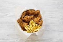 Stekt kycklingtrumpinnar, kryddiga vingar, pommes frites och anbudremsor i pappers- ask över vit träbakgrund, bästa sikt plan la arkivbilder