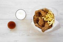 Stekt kycklingtrumpinnar, kryddiga vingar, pommes frites och anbudremsor i pappers- ask, sås och kallt öl över den vita träbackgr arkivbilder