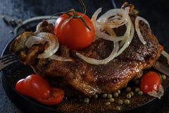 Stekt lamm med grönsaker Stekt kött på en svart bakgrund Arkivbilder
