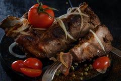 Stekt lamm med grönsaker Stekt kött på en svart bakgrund Stycke av kött på gaffeln Royaltyfria Bilder