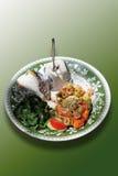 Stekt lax med scampi, spenat, oliv och potatisar med sourcr Arkivfoto