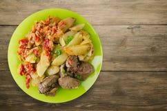 Stekt lever med potatisar och lät småkoka tomater Arkivfoton
