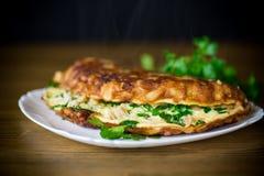 Stekt omelett med blomkålen och gräsplaner i en platta royaltyfri foto