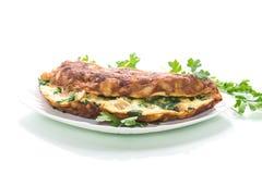 Stekt omelett med blomkålen och gräsplaner i en platta royaltyfria foton