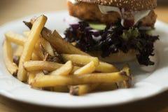 Stekt potatis och hamburgare med fisken och grönsaken royaltyfria bilder