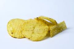 Stekt potatis, r�fflade chips p� en vit bakgrund. Stock Photos