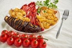 Stekt potatisar, aubergine, spansk peppar och blomkål på den vita plattan som dekoreras med silvergaffeln och körsbärsröda tomate Royaltyfria Foton