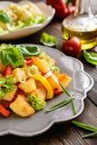 Stekt potatissallad med grönsallat, peppar, löken och den bakade fisken fi Arkivbild