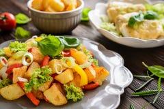 Stekt potatissallad med grönsallat, peppar, löken och den bakade fisken fi Arkivbilder