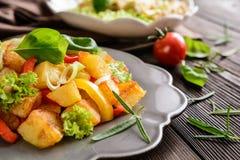 Stekt potatissallad med grönsallat, peppar, löken och den bakade fisken fi Royaltyfri Foto