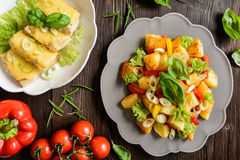 Stekt potatissallad med grönsallat, peppar, löken och den bakade fisken fi Royaltyfria Bilder