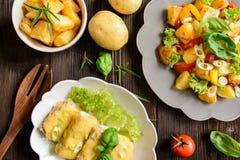 Stekt potatissallad med grönsallat, peppar, löken och den bakade fisken fi Royaltyfri Fotografi