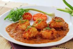 Den stekte räkan klumpa ihop sig i röd curry. Arkivbild