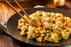 Stekt risnasigoreng med höna och grönsaker på en platta royaltyfria bilder