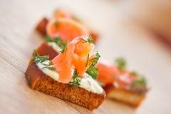 Stekt rostat bröd med den rimmade laxen Arkivfoto
