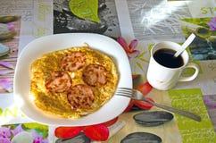 Stekt skinka med ägg, i en platta på tabellen med en bordduk och ett kaffe Hemlagad frukost Verkligt, inte arrangerat foto arkivfoton