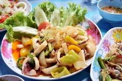 Stekt tioarmad bläckfisk i gul curry på maträttinnehav vid handen av mor Royaltyfria Bilder