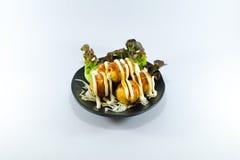 Stekt tioarmad bläckfiskboll med kräm- sås på vit bakgrund Arkivbild
