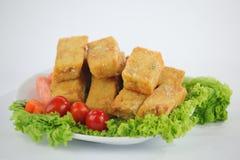 Stekt tofu med grönsallat, tomater och moroten på den vita plattan Arkivbilder