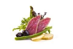 Stekt tonfiskbiff med potatisar, haricot vert och oliv på vita lodisar royaltyfri foto