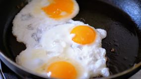 Stekt tre ägg som stekas i en panna stock video