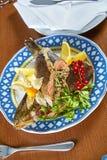 Stekt välfylld fisk på en festlig meny för uppläggningsfat arkivfoton