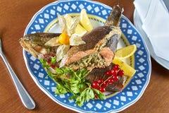 Stekt välfylld fisk på en festlig meny för uppläggningsfat arkivbilder