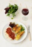 Stekt zucchini med ris och sause, nya örter och ett exponeringsglas av vin Fotografering för Bildbyråer