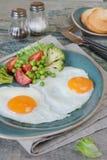 Stekte ägg, grönsaker och toastes Arkivfoton