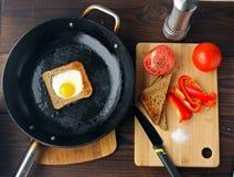 Stekte ägg i bröd i en panna med klippta grönsaker på tabellen arkivbild