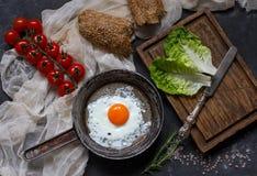 Stekte ägg i en stekpanna med bröd, körsbärsröda tomater och grönsallat på den bästa sikten för mörk bakgrund Royaltyfria Bilder