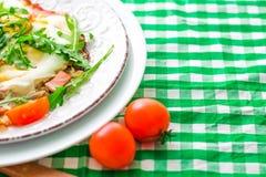 Stekte ägg med arugula och tomater som är körsbärsröda på den vita plattan och den rutiga torkduken kopiera avstånd royaltyfria bilder