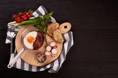 Stekte ägg med bacon på ett bräde i en panna arkivbild