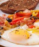 Stekte ägg med bacon, tomater, oliv och skivor av ost Arkivbilder