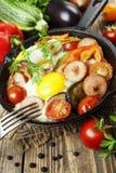 Stekte ägg med grönsaker och korven Royaltyfria Bilder