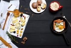 Stekte ägg med korvar i en stekpanna och typer av ost royaltyfri fotografi
