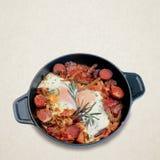 Stekte ägg med korvar i en svart panna Royaltyfri Bild