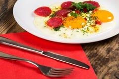 Stekte ägg med korven i den vita maträtten Arkivbilder