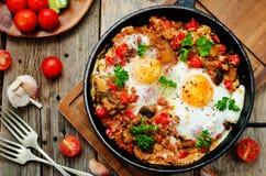 Stekte ägg med peppar, tomater, quinoaen och champinjoner royaltyfria bilder