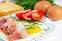 Stekte ägg med skinka och tomater Arkivbild